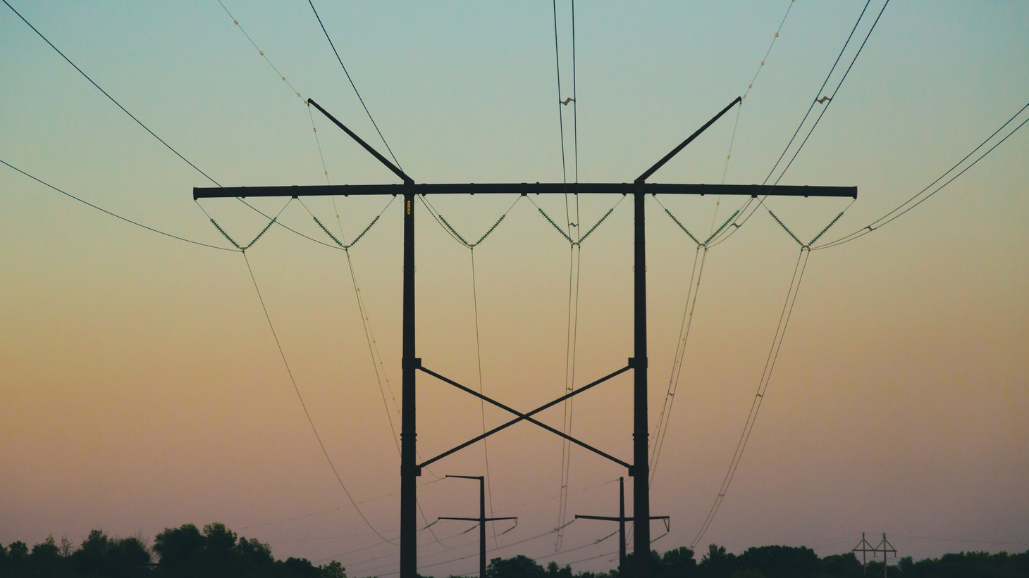 Electrical power lines along Great River Road near Trempealeau, Wisconsin, at sunset. Around the U.S., aging power grids can't keep up with the growing number of weather disasters caused by climate change.