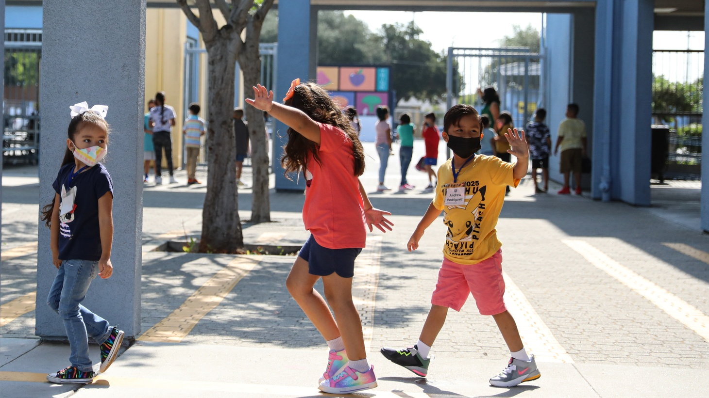 Students wave to their friends as they line up to receive a snack at Montara Avenue Elementary School in South Gate, August 16, 2021.