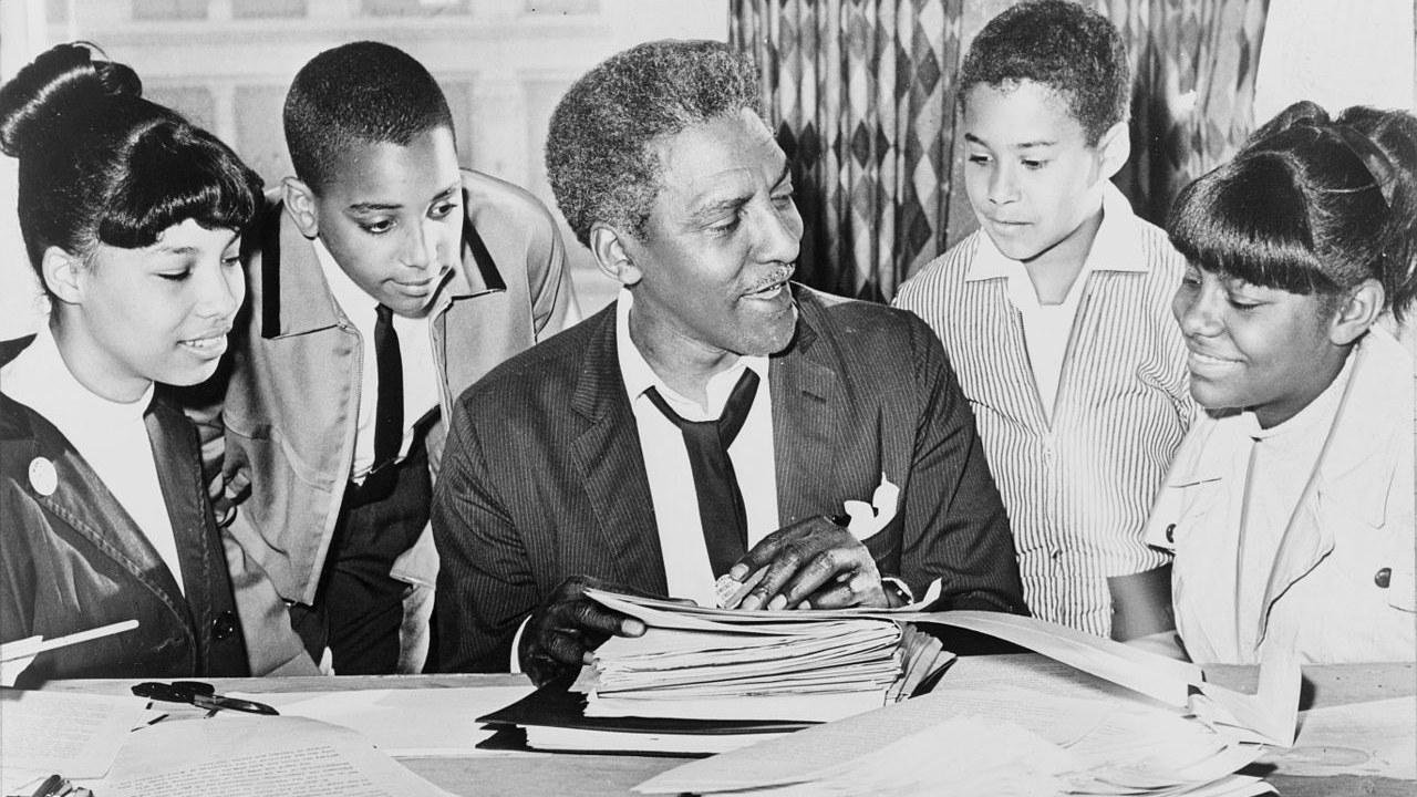 Bayard Rustin (center) speaking with (left to right) Carolyn Carter, Cecil Carter, Kurt Levister, and Kathy Ross.
