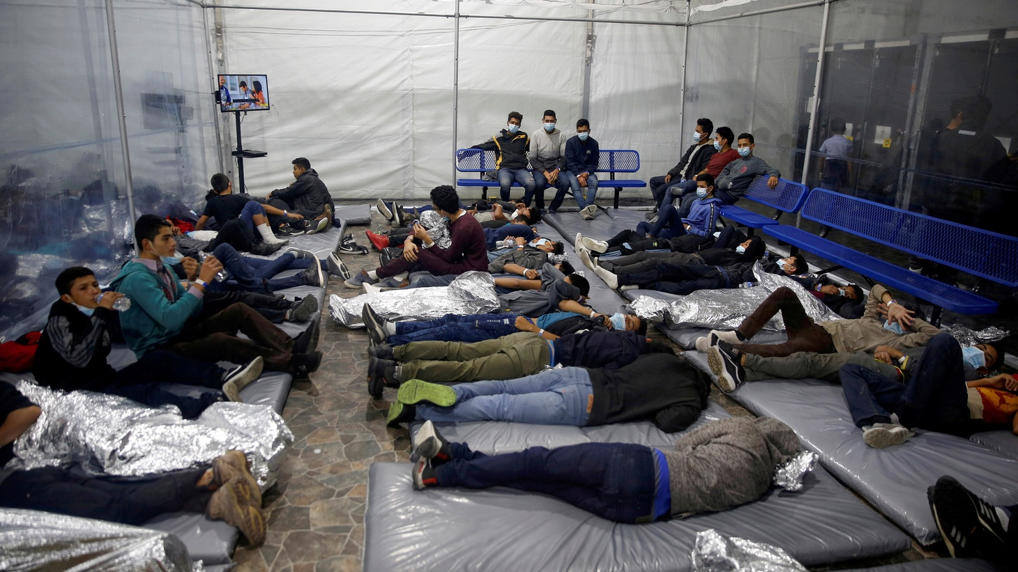 Young migrants lie inside a pod at the Donna Department of Homeland Security holding facility. It's the main detention center for unaccompanied children in the Rio Grande Valley, run by U.S. Customs and Border Protection, in Donna, Texas, Tuesday, March 30, 2021.