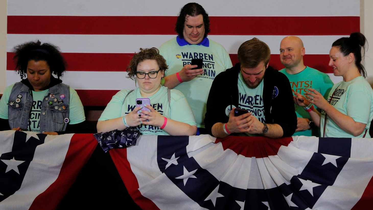 Supporters of Democratic 2020 U.S. presidential candidate and U.S. Senator Elizabeth Warren (D-MA) look at their mobile phones before she speaks at her Iowa Caucus rally in Des Moines, Iowa, U.S., February 3, 2020. Picture taken February 3, 2020.