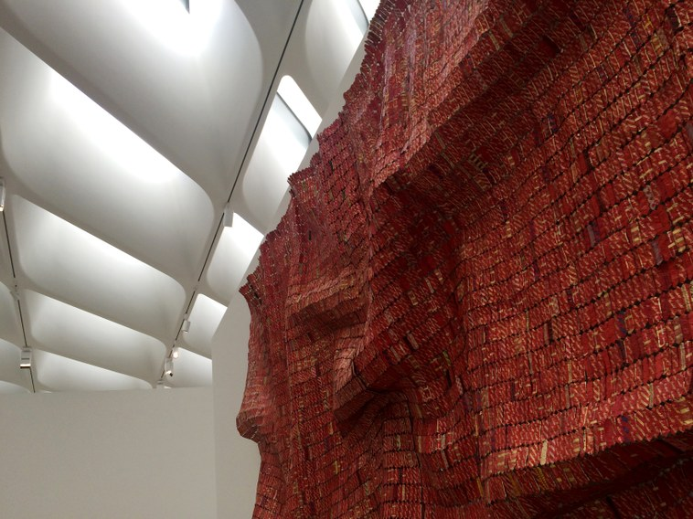 """Ghanian artist El Anatsui wove thousands of discarded liquor labels together for this tapestry on display now at The Broad. The so-called """"veil"""" of the museum can be seen in the background."""