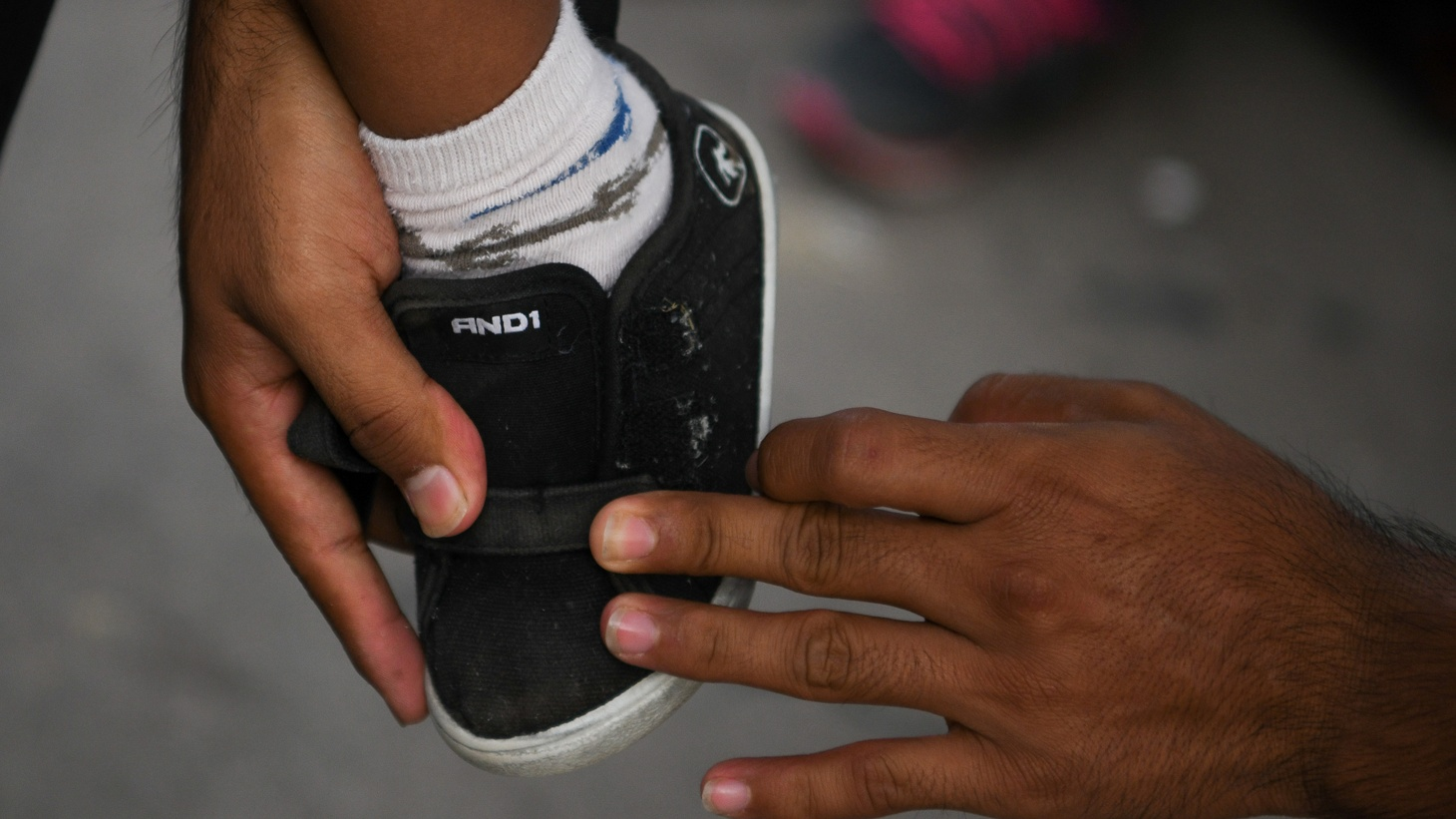 A Honduran asylum seeker puts a shoe on his 3-year-old son's foot. McAllen, Texas, U.S., May 16, 2019.