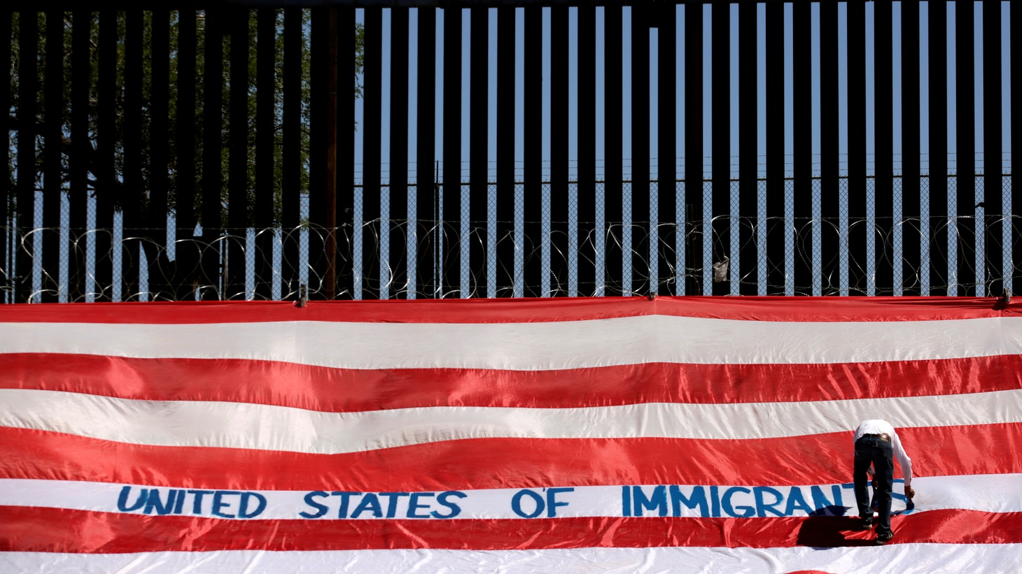 Roberto Marquez, known as Roberz, writes on a large U.S. flag as part of a protest called 'United States of Immigrants', aimed to demand respect for the migrants, near a border wall in El Paso, Texas, as pictured from Ciudad Juarez, Mexico June 6, 2019.