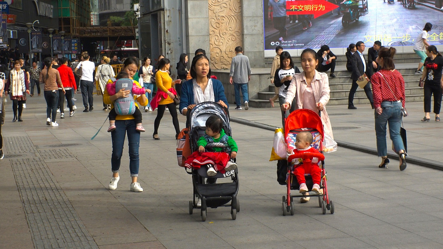 Parents walk with their young children in the Laojie area of China.