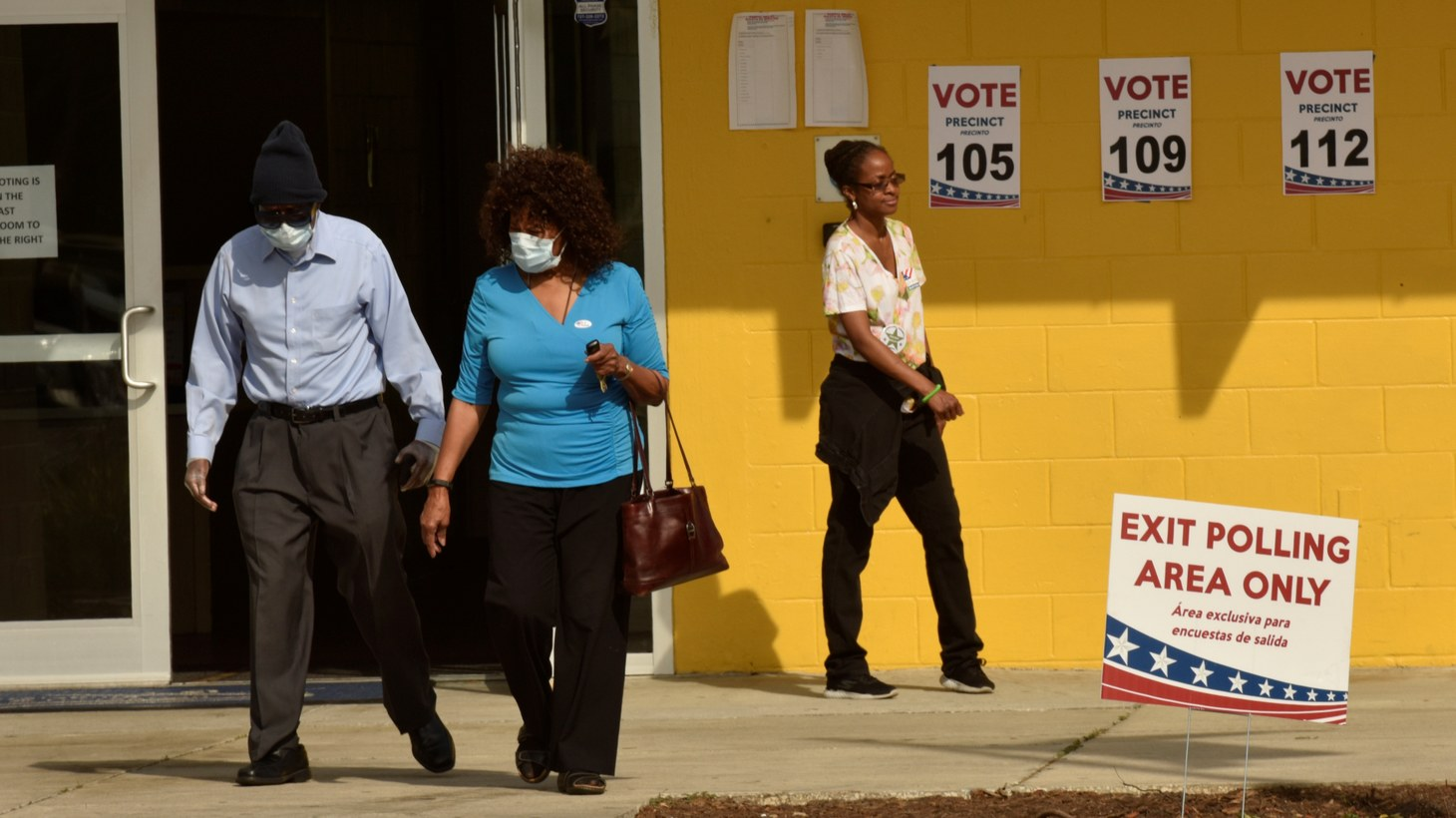 Voters wearing protective masks, due the outbreak of coronavirus disease, walk past election official Brianna Peterson after voting in the municipal and presidential primary elections at their polling center in St. Petersburg, Florida March 17, 2020.