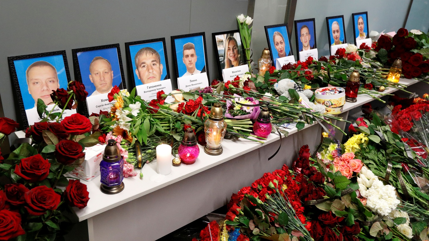 Flowers and candles are placed in front of the portraits of the flight crew members of the Ukraine International Airlines Boeing 737-800 plane that crashed in Iran, at a memorial at the Boryspil International airport outside Kiev, Ukraine. January 8, 2020.