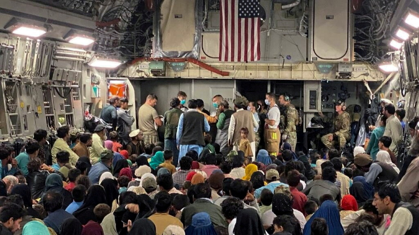 A newborn baby is looked after — before taking off with other Afghan evacuees on a C-17 Globemaster III at a Middle East staging area, August 23, 2021.