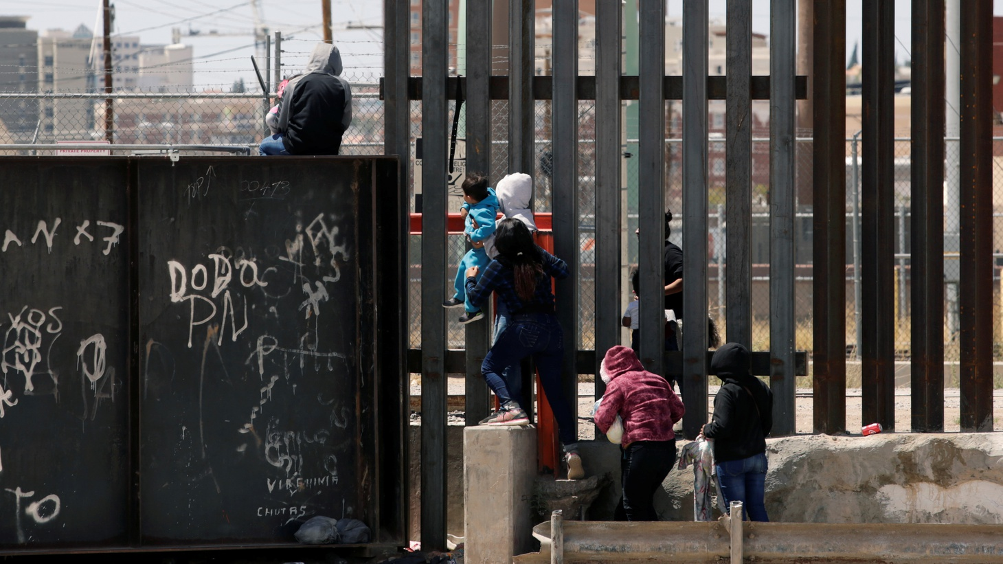 Migrants jump over the border wall to cross the U.S. from Mexico, in Ciudad Juarez, Mexico, June 22, 2019.