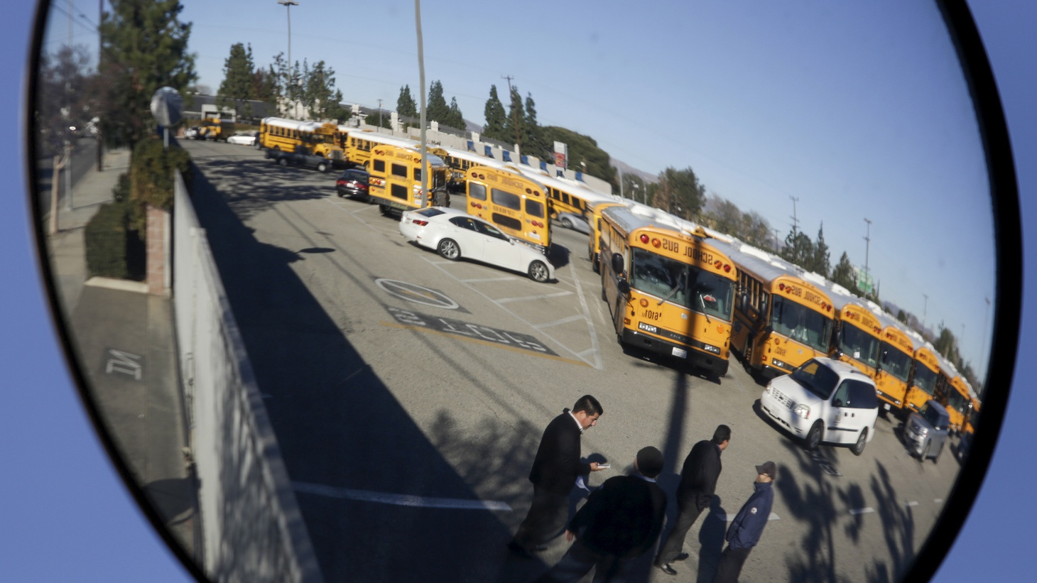A Los Angeles Unified School District (LAUSD) school bus yard is reflected in a mirror in the North Hills neighborhood of Los Angeles.