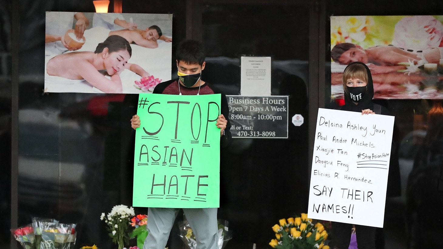 After dropping off flowers, Jesus Estrella, left, and Shelby S., right, stand in support of the Asian and Hispanic community outside Young's Asian Massage, where four people were killed on Wednesday, March 17, 2021, in Acworth, Georgia. At least eight people were found dead at three different spas in the Atlanta area Tuesday by suspected killer Robert Aaron Long.
