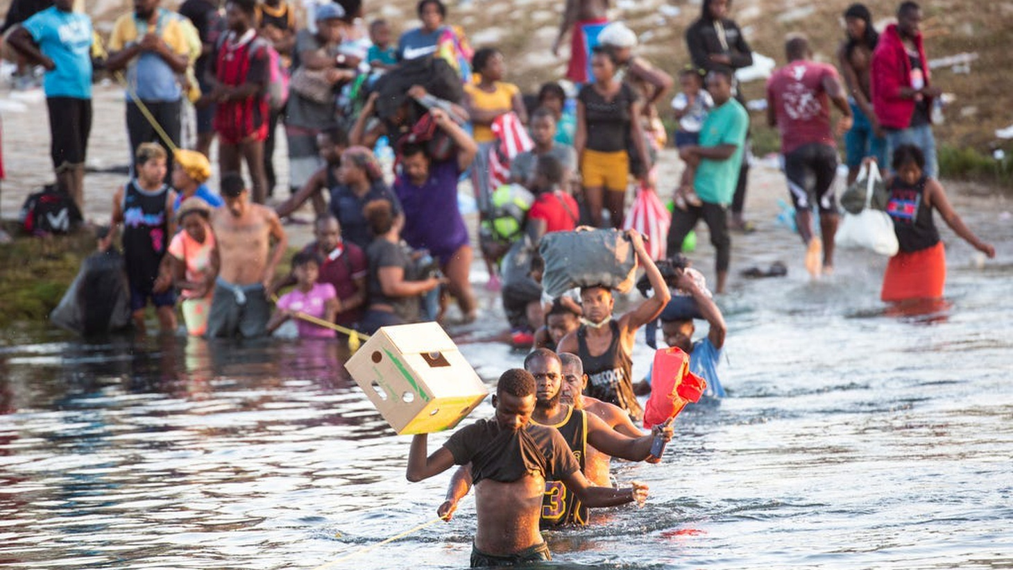 Haitian migrants cross the Rio Grande south into Ciudad Acuna from Del Rio, Texas, as they leave the migrant encampment underneath the Del Rio International Bridge after concerns of food scarcity and expulsions to Haiti on Sept. 20, 2021.