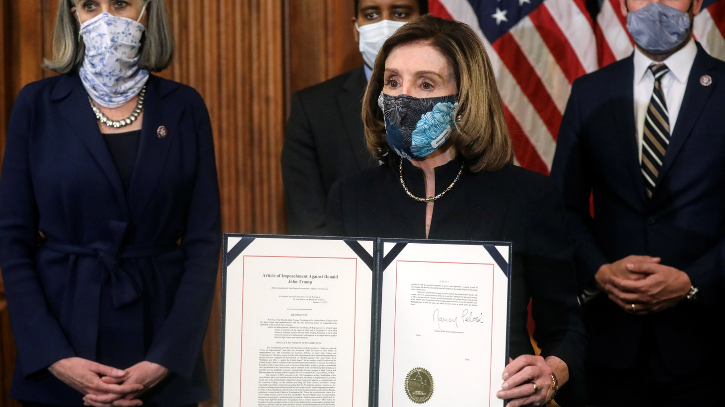 U.S. House Speaker Nancy Pelosi (D-CA) shows the article of impeachment against U.S. President Donald Trump after signing it in an engrossment ceremony, at the U.S. Capitol in Washington January 13, 2021.