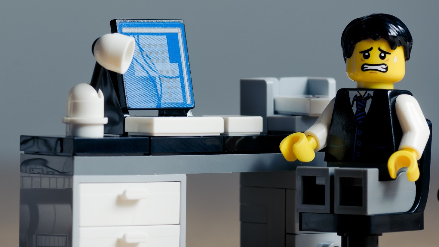 A LEGO of a stressed man at a computer.