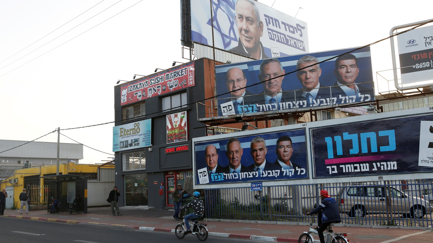 Cyclists ride past a Likud party election campaign billboard depicting Israeli Prime Minister Benjamin Netanyahu and billboards depicting Benny Gantz, leader of Blue and White party, together with his top party candidates Moshe Yaalon, Yair Lapid and Gaby Ashkenazi, in Petah Tikva, Israel April 7, 2019.