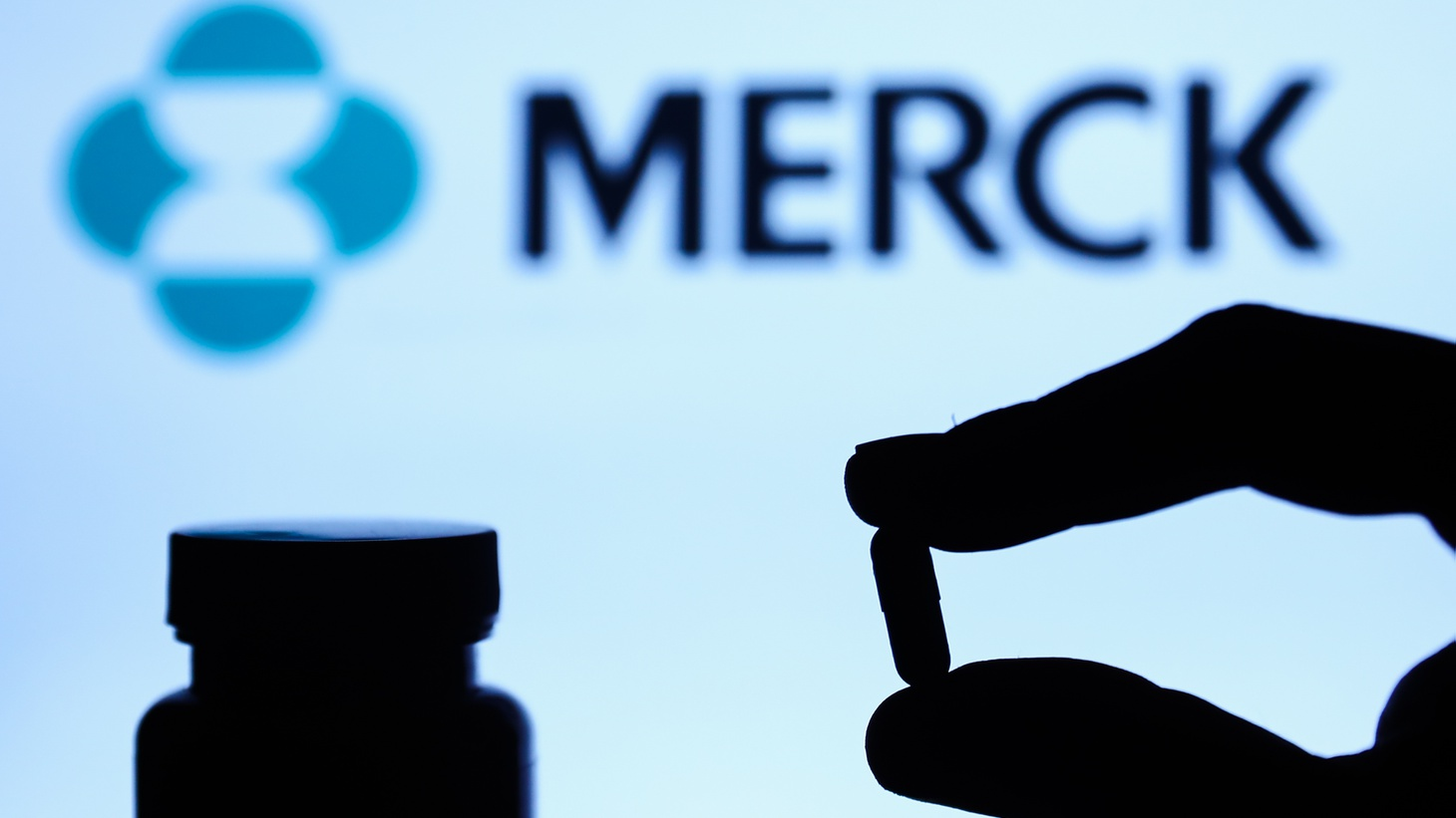 A pill is seen with a Merck logo displayed on a screen in the background, October 4, 2021. This could be the first oral medication for treating COVID-19 — if approved by the FDA.