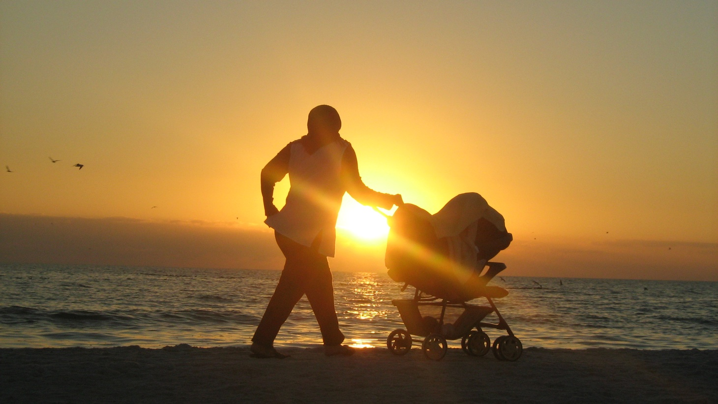 A mother pushing a baby carriage on Lido Beach in Sarasota, Florida.