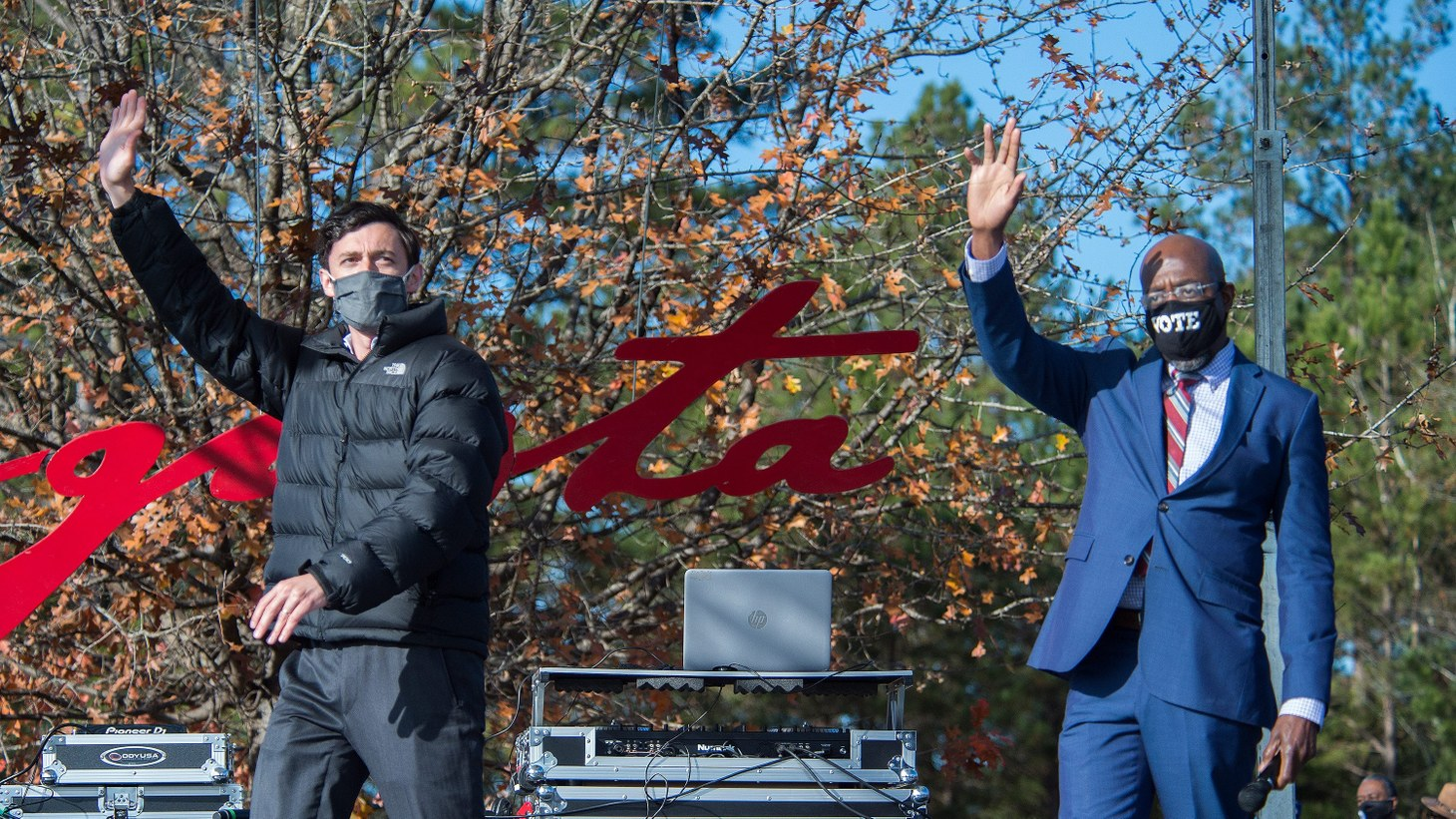 Jon Ossoff, left, and Raphael Warnock wave to the crowd during a campaign rally in Augusta, Ga., Monday morning January 4, 2021.