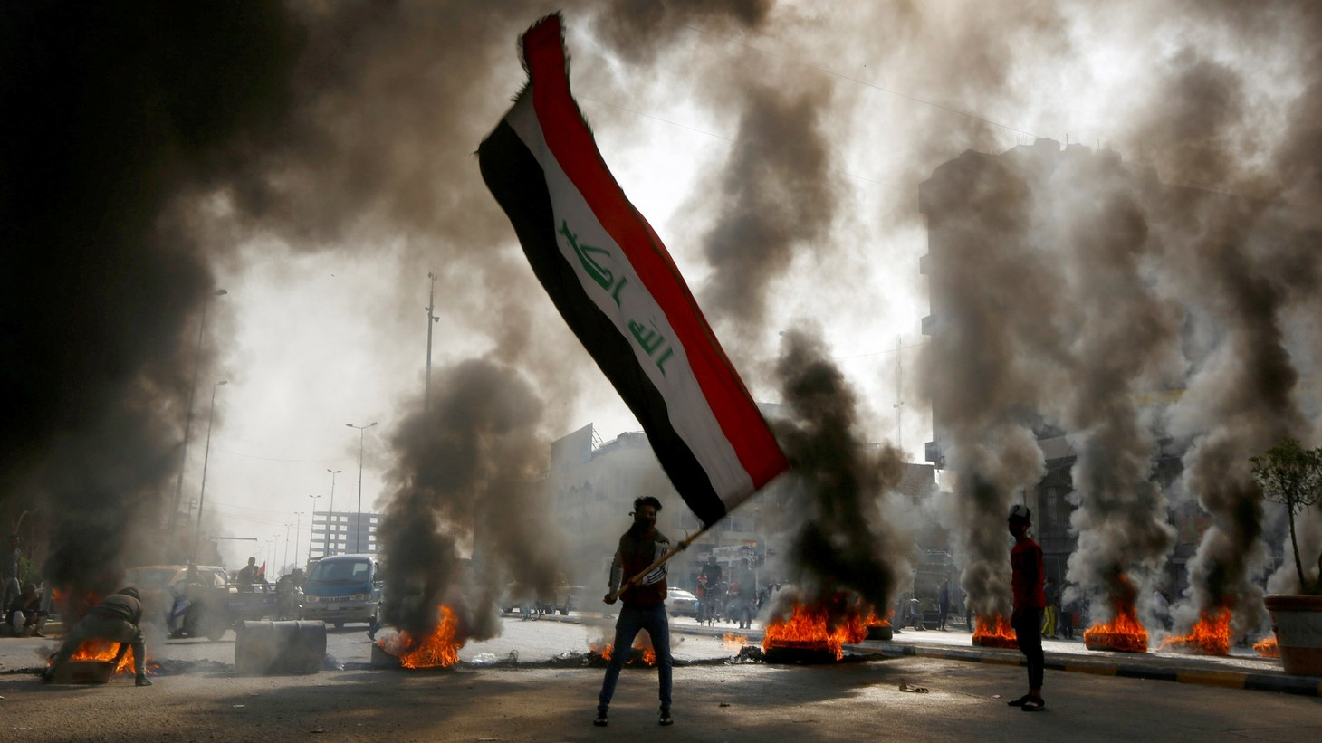 A protester holds an Iraqi flag amid a cloud of smoke from burning tires during ongoing anti-government protests in Najaf, Iraq November 26, 2019.