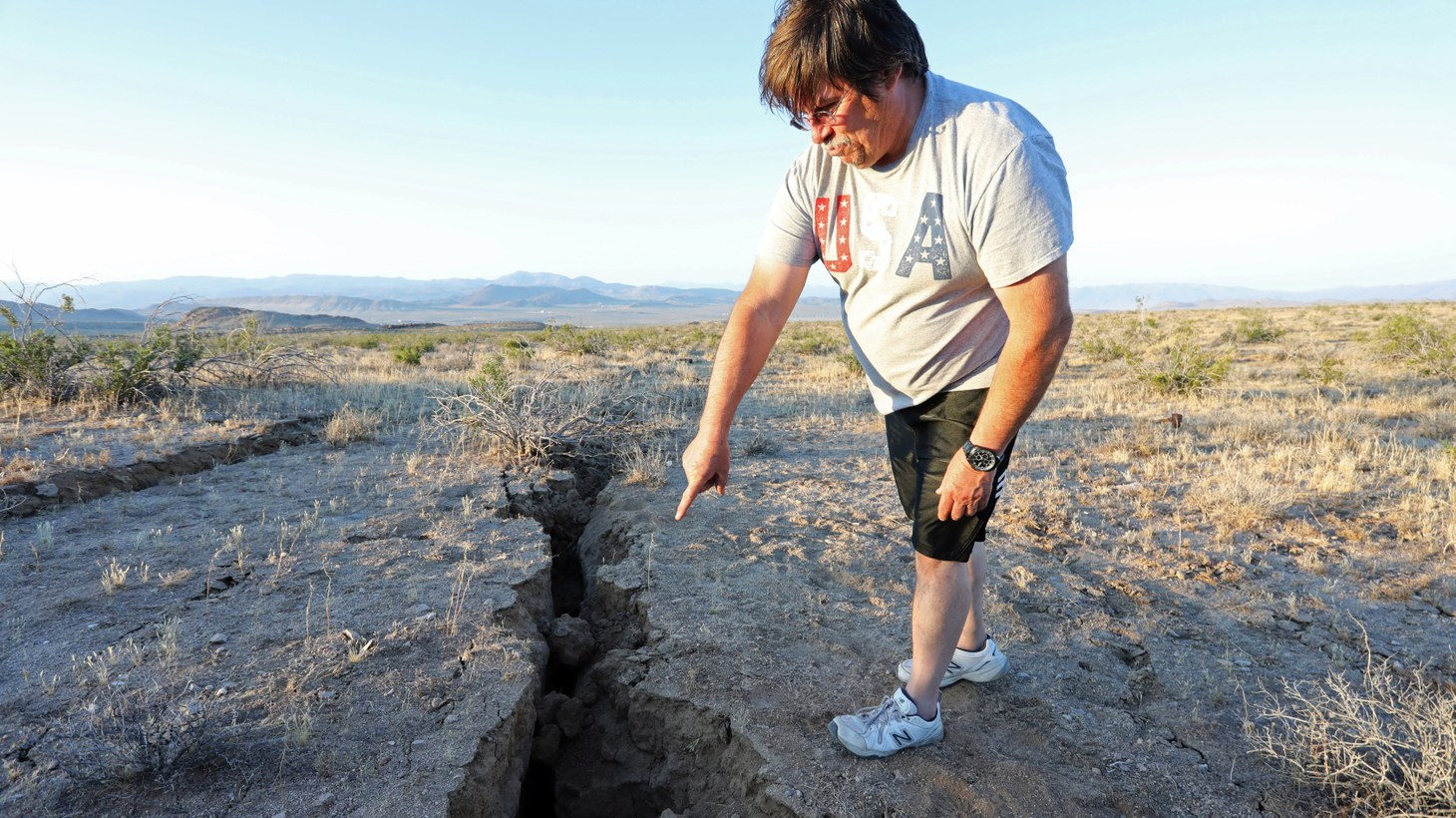 A man looks into a fissure that opened in the desert during a powerful earthquake that struck Southern California, near the city of Ridgecrest, California, U.S., July 4, 2019.