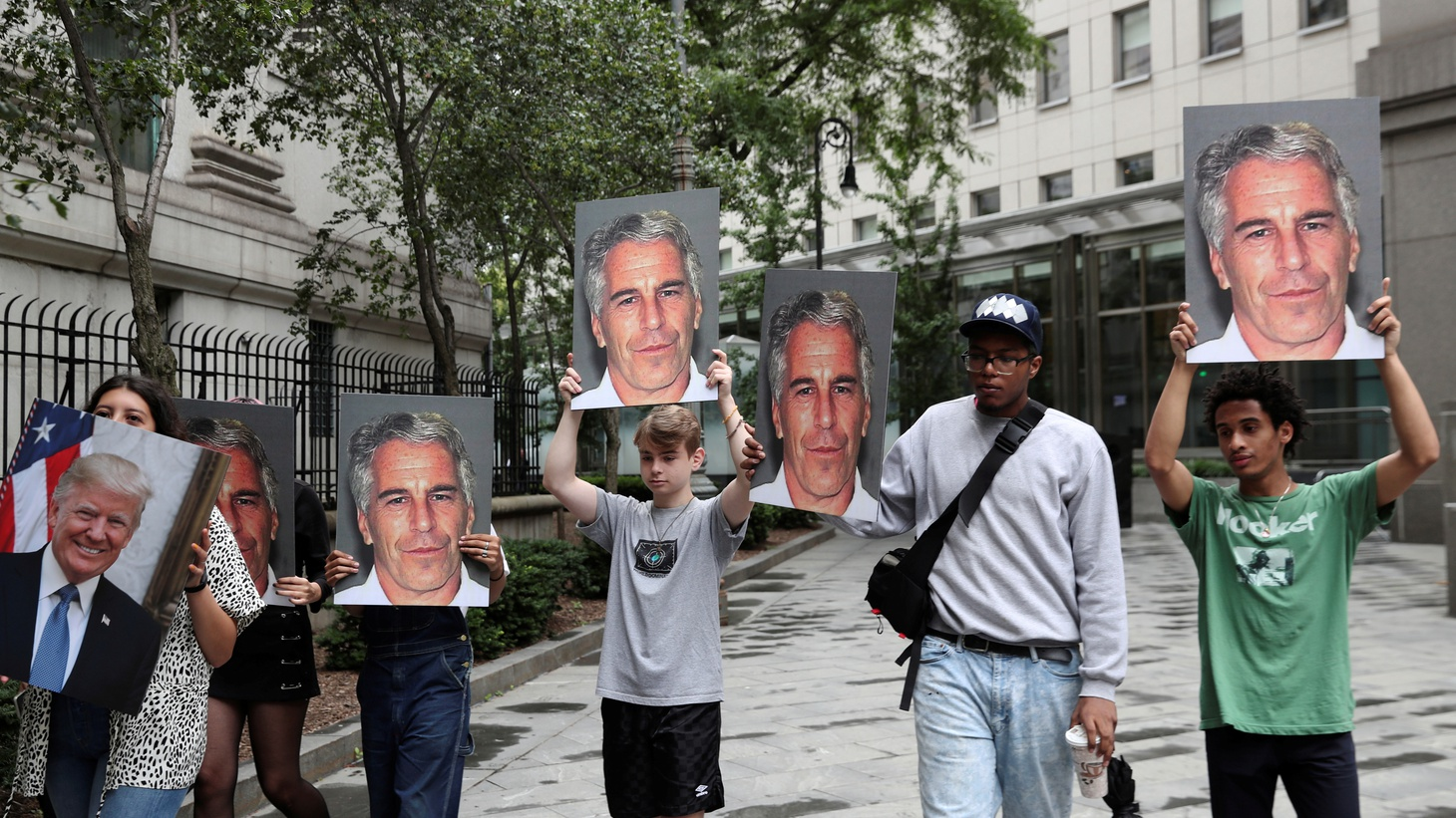 Demonstrators hold signs aloft protesting Jeffrey Epstein, as he awaits arraignment in the Southern District of New York on charges of sex trafficking of minors and conspiracy to commit sex trafficking of minors, in New York, U.S., July 8, 2019.