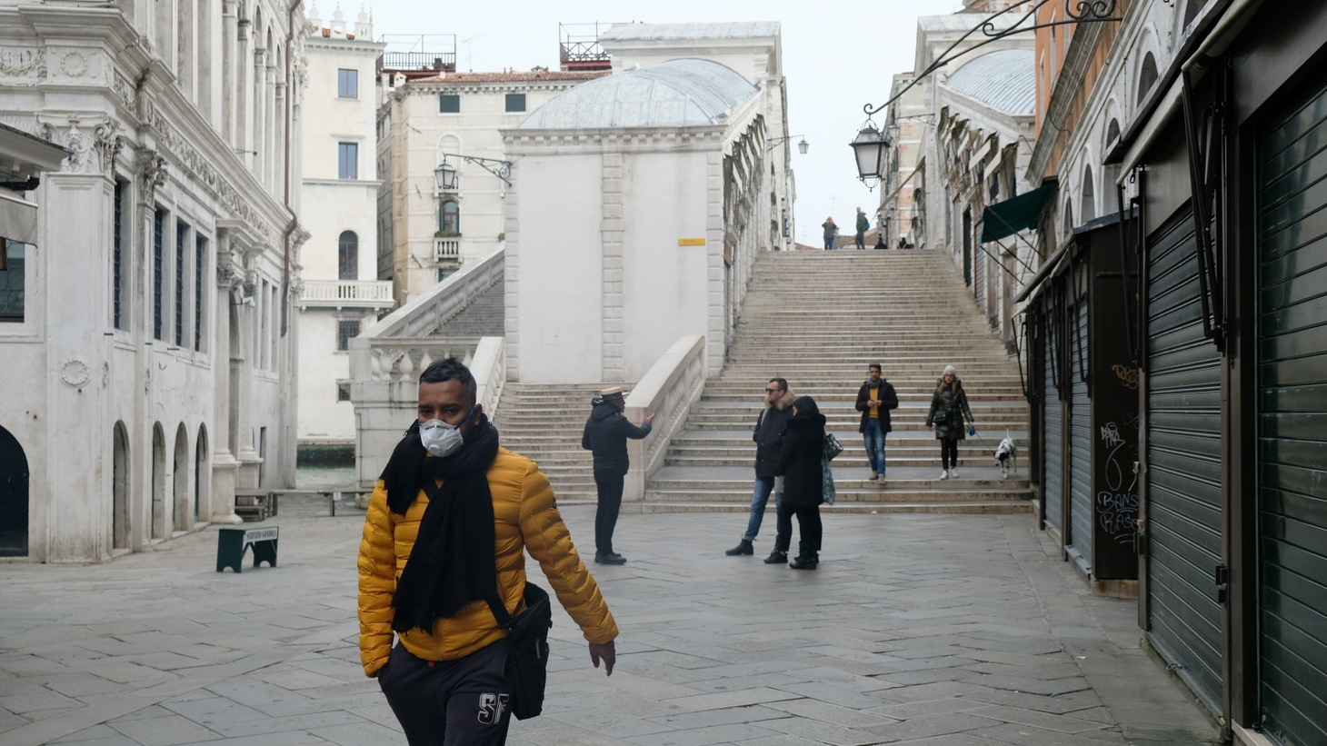 A man wearing a protective face mask walks through a street after the Italian government imposed a virtual lockdown on the north of Italy, including Venice, to try to contain a coronavirus outbreak. March 9, 2020.