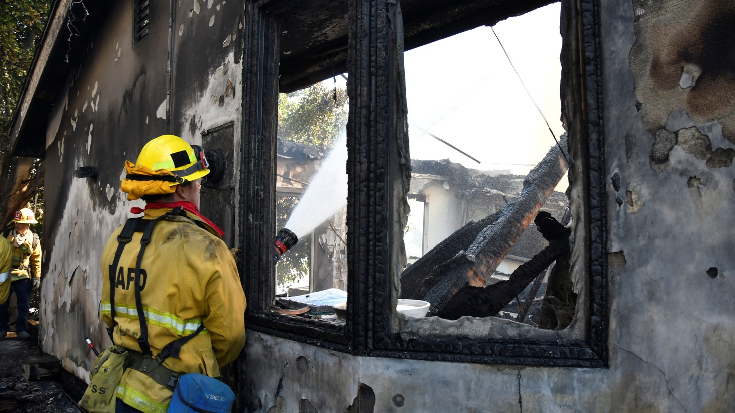 A firefighter douses water on a house after it was burned by the wind-driven Getty Fire in West Los Angeles, California, U.S. October 28, 2019.