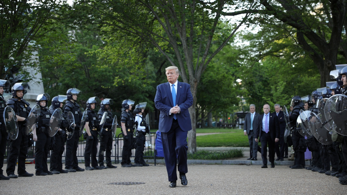 U.S. President Donald Trump walks between lines of riot police in Lafayette Park across from the White House, after walking to St. John's Church for a photo opportunity during protests in the wake of the death of George Floyd. June 1, 2020.