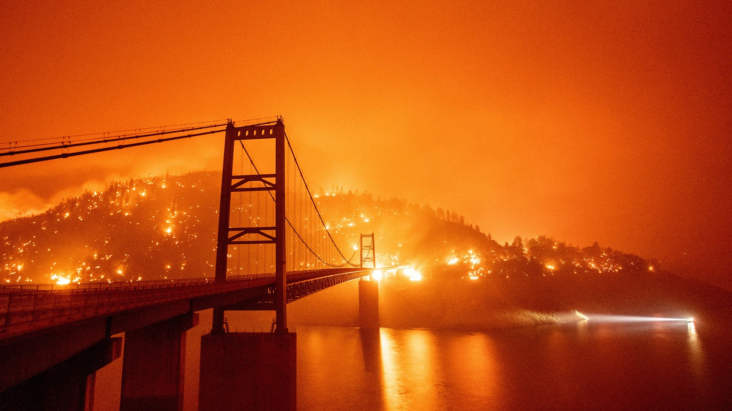 A boat motors by as the Bidwell Bar Bridge is surrounded by fire in Lake Oroville during the Bear Fire in Oroville, California on September 9, 2020. Dangerous dry winds whipped up California's record-breaking wildfires and ignited new blazes Tuesday, as hundreds were evacuated by helicopter and tens of thousands were plunged into darkness by power outages across the western United States.
