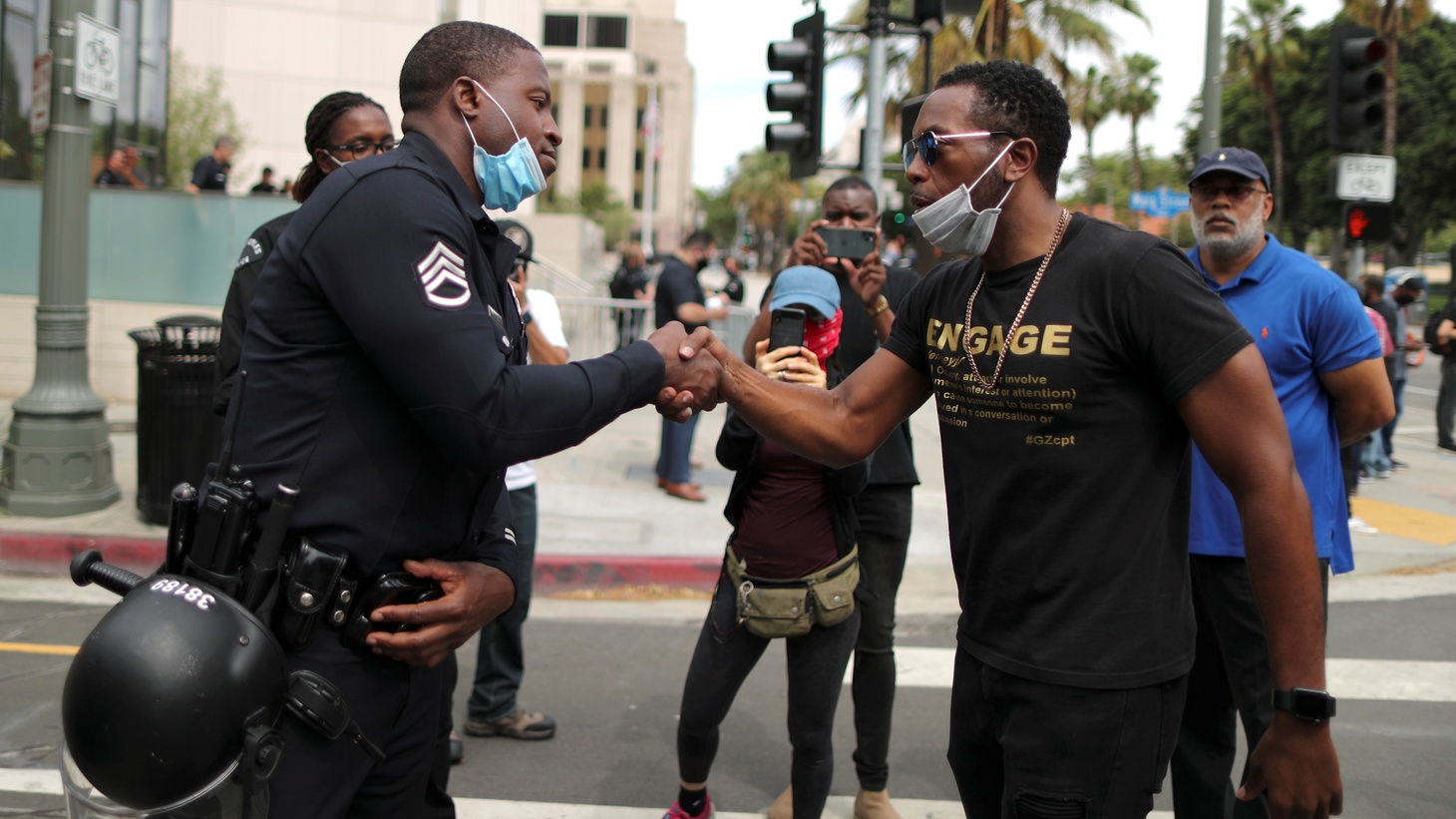 A police officer shakes hands with a demonstrator during a protest against the death of George Floyd, outside LAPD headquarters in Los Angeles, California, U.S. June 2, 2020.