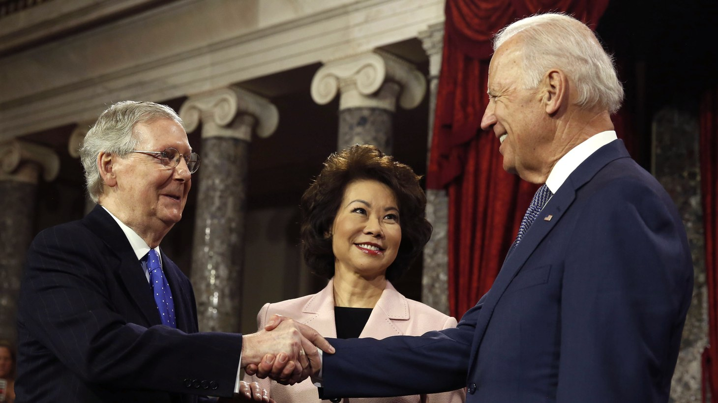 U.S. Senate Majority Leader Mitch McConnell (L) shakes hands, after he ceremonially swore-in, with Vice President Joseph Biden (R) in the Old Senate Chamber on Capitol Hill in Washington January 6, 2015. Holding the Bible is McConnell's wife, former Secretary of Labor Elaine Chao.