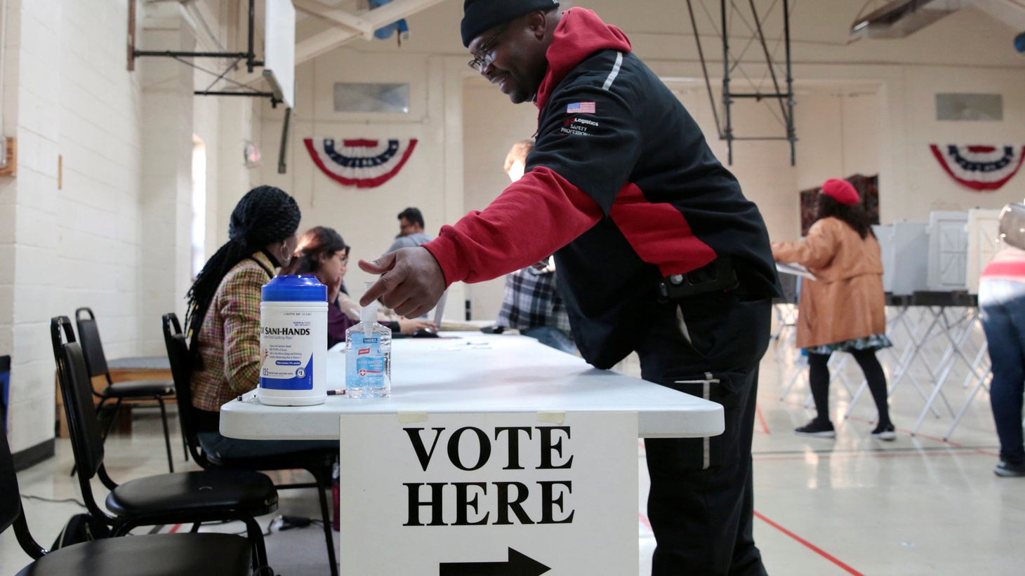 A voter uses the hand sanitizer on the table as voters cast their ballots in the Democratic primary in Warren, Michigan, U.S. March 10, 2020.