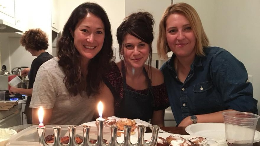 A Hanukkah celebration in the U.S. among KCRW producers Jenny Hamel (left), Yael Even Or (center), and Michell Eloy (right).