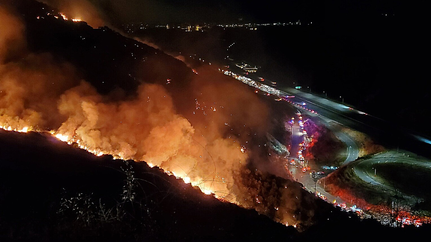 Firefighters and authorities work to extinguish a fire near the Getty Center in Los Angeles, June 10, 2020.