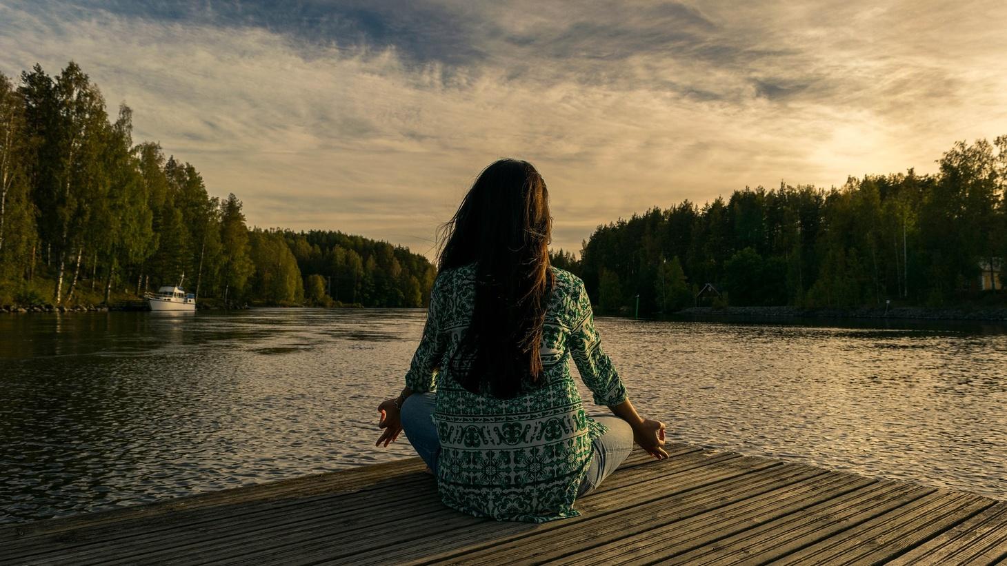 A woman meditating outdoors.