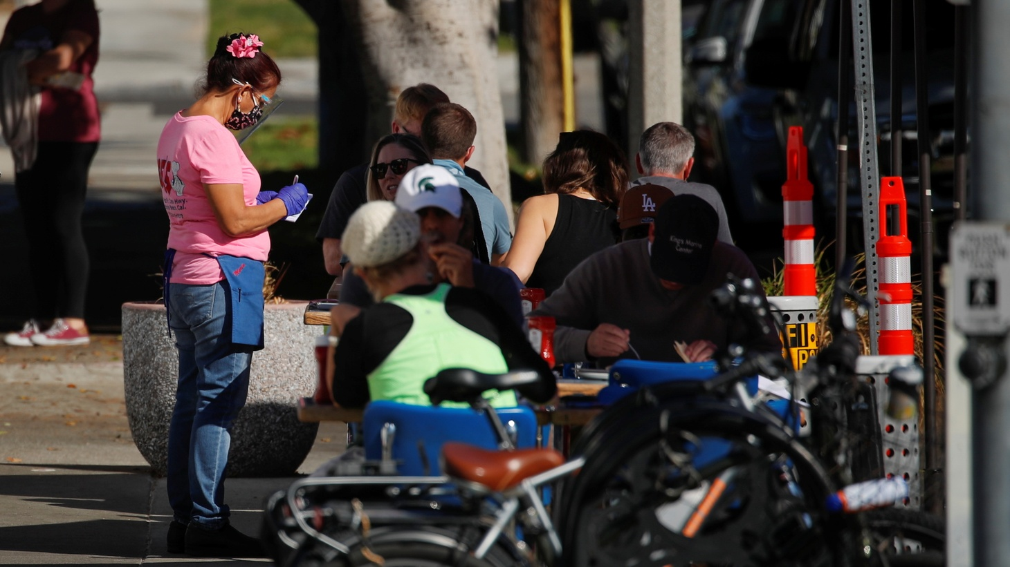 "A waitress takes customers' orders along the sidewalk outside ""Eat at Joes'' restaurant in Redondo Beach, California."