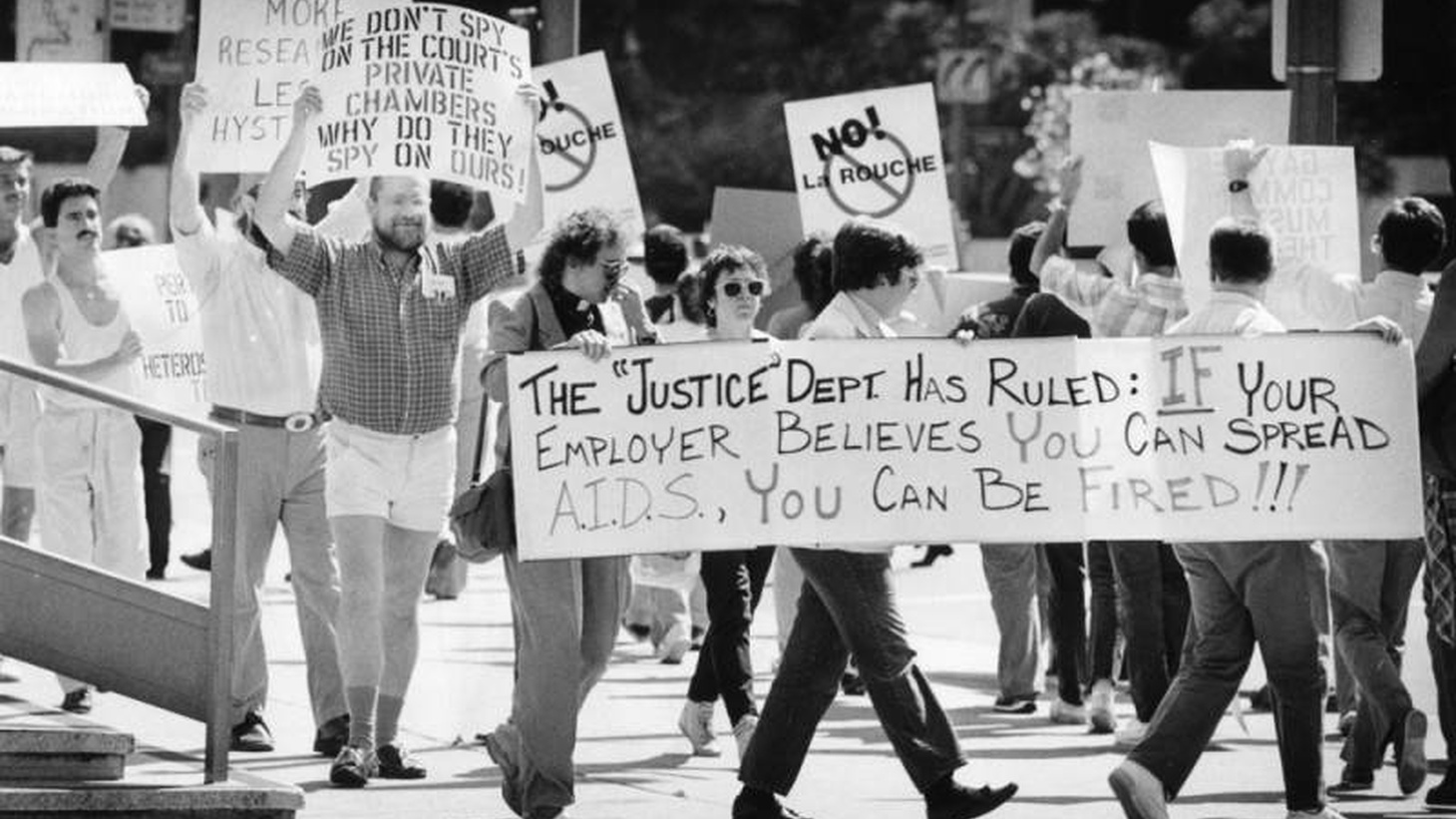 "July 2, 1986 - A protest at the Federal Building in Los Angeles, Calif. Some signs read, ""The 'Justice' Dept. has ruled: If your employer believes you can spread A.I.D.S., You can be fired!!!"""