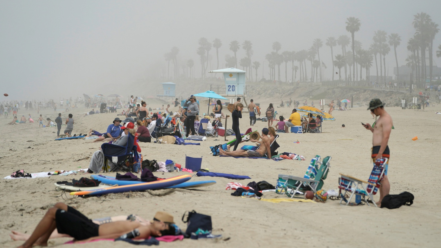 People sit in groups at Huntington City Beach, California, during the outbreak of the coronavirus disease (COVID-19), April 25, 2020.