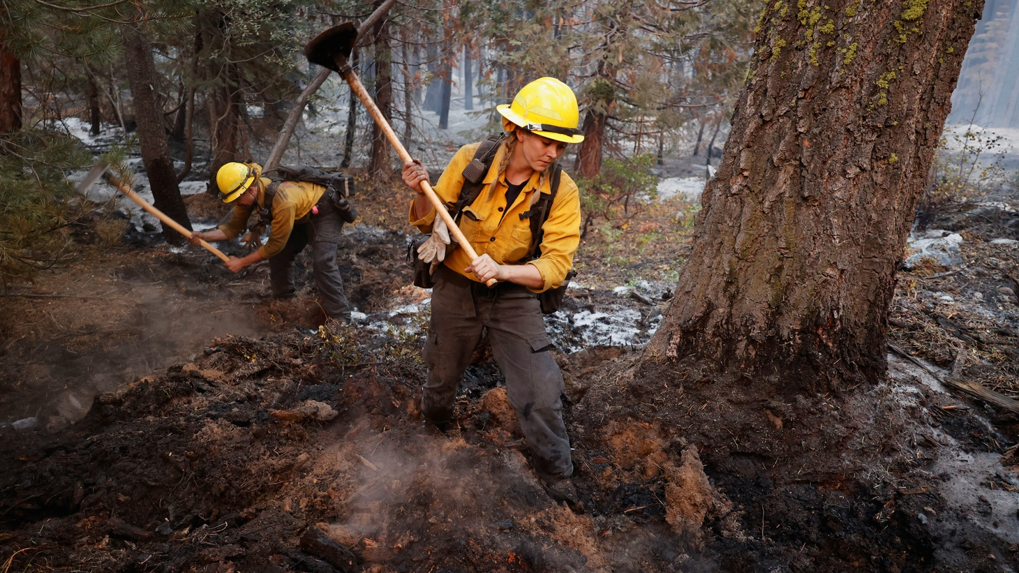 Firefighters Stephanie Lockhart and Dustin Peters of North Tahoe Fire break up smoldering areas after the Caldor Fire moved through the area, in South Lake Tahoe, California, U.S., September 1, 2021.