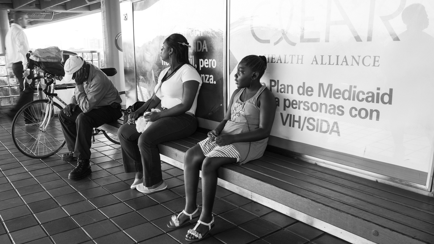 People sitting in front of a Medicaid sign.
