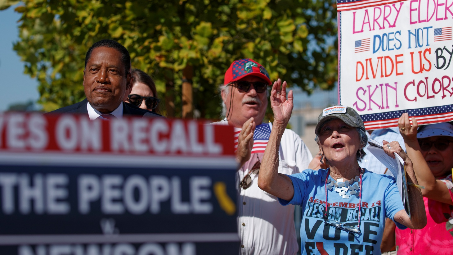 """During a recall campaign rally by gubernatorial candidate Larry Elder, a woman holds a sign saying, """"Larry Elder does not divide us by skin color,"""" in Monterey Park, California, U.S., September 13, 2021."""