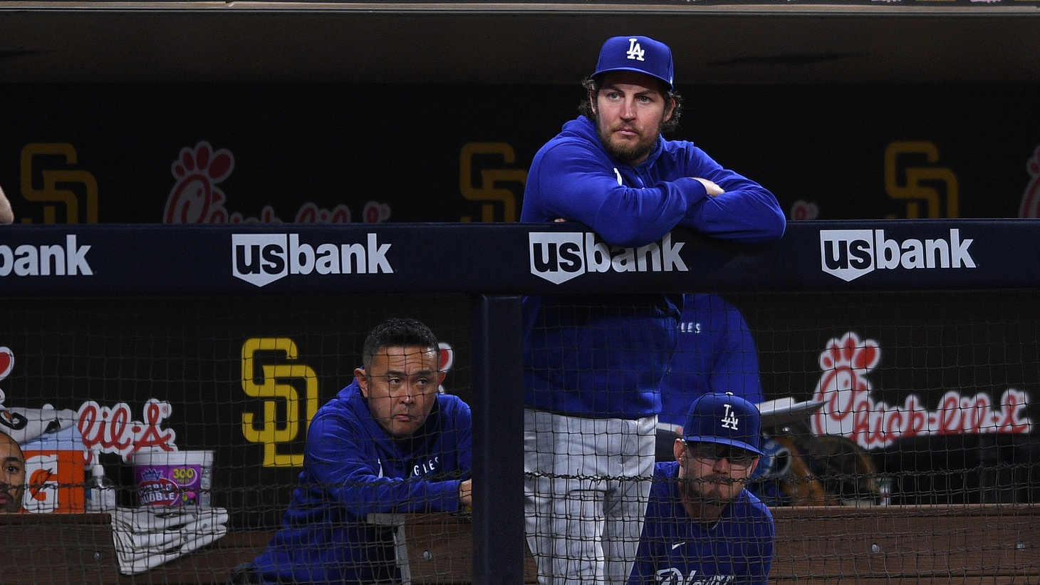 Los Angeles Dodgers starting pitcher Trevor Bauer (top) looks on from the dugout during the fifth inning against the San Diego Padres at Petco Park, San Diego, California, Jun 22, 2021.