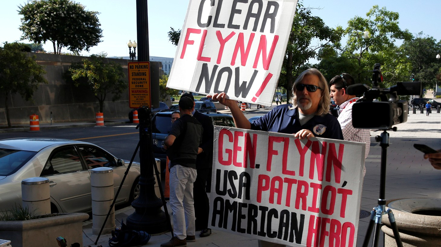 A supporter of former National Security Adviser Michael Flynn holds up placards as Flynn arrives for a status hearing, July 10, 2018.