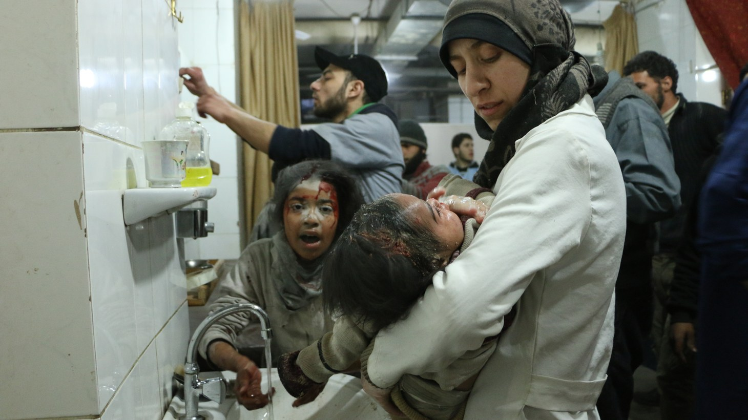 Al Ghouta, Syria - Dr. Amani (R) treats an injured baby amongst other medical staff and victims.