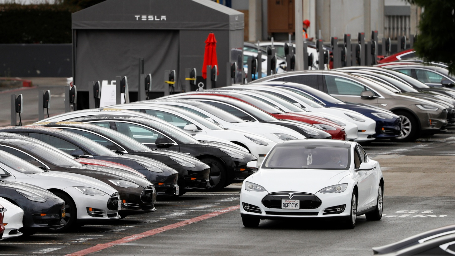 A Tesla Model S electric vehicle drives along a row of occupied superchargers at Tesla's primary vehicle factory after CEO Elon Musk announced he was defying local officials' restrictions against the coronavirus disease (COVID-19) by reopening the plant in Fremont, California, U.S. May 12.