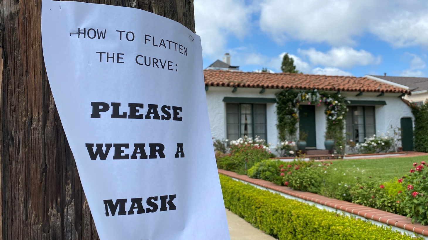 A Los Angeles neighborhood sign asks people to wear masks as the global spread of COVID-19 continues.