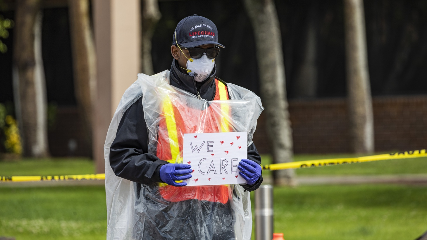 "At a COVID-19 testing site in South LA, a man wears a medical mask and gloves. His sign says ""we care."" April 8, 2020."