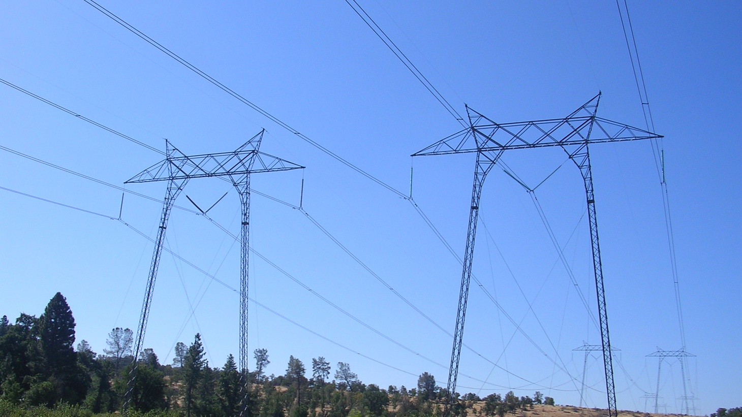Pacific Gas and Electric 500 kV AC power lines crossing California State Route 36 north of Table Mountain, cutting through the woodlands of the Sierra foothills east of Red Bluff, Tehama County, Northern California.