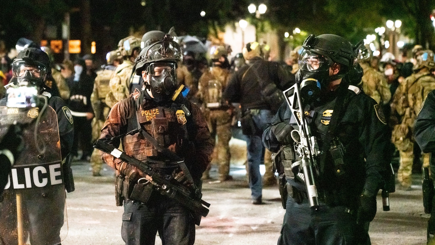 Federal agents stand outside the federal courthouse in Portland, Oregon, July 26, 2020. Their uniforms are colored red by the detonation of what appeared to be smoke or dust bombs thrown by protesters.