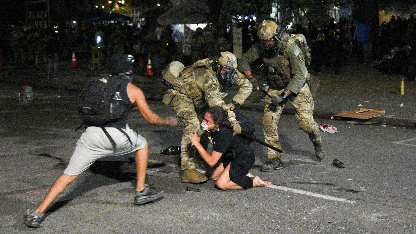 """Federal agents try to detain a woman while a protester tries to """"de-arrest"""" her on July 27, 2020, outside of the federal courthouse in Portland, Oregon."""